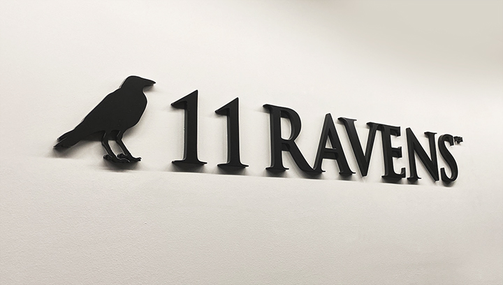 11 Ravens interior logo sign in a black color made of acrylic for corporate branding indoors