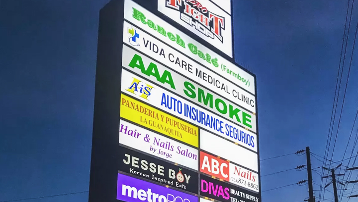 commercial center pylon sign displaying multiple brand names made of acrylic and aluminum