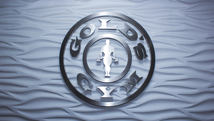 Gold's Gym metal interior sign in a round shape displaying the company logo made of brushed aluminum for corporate branding