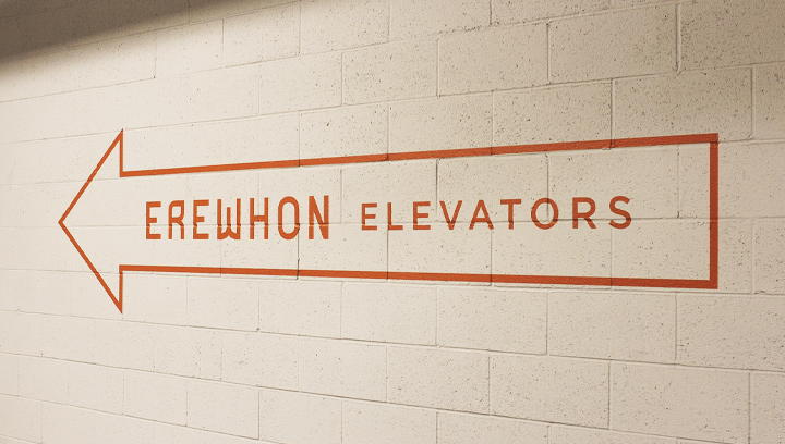 Erewhon interior wayfinding signage painted in orange color made of opaque vinyl for directing visitors to the elevator