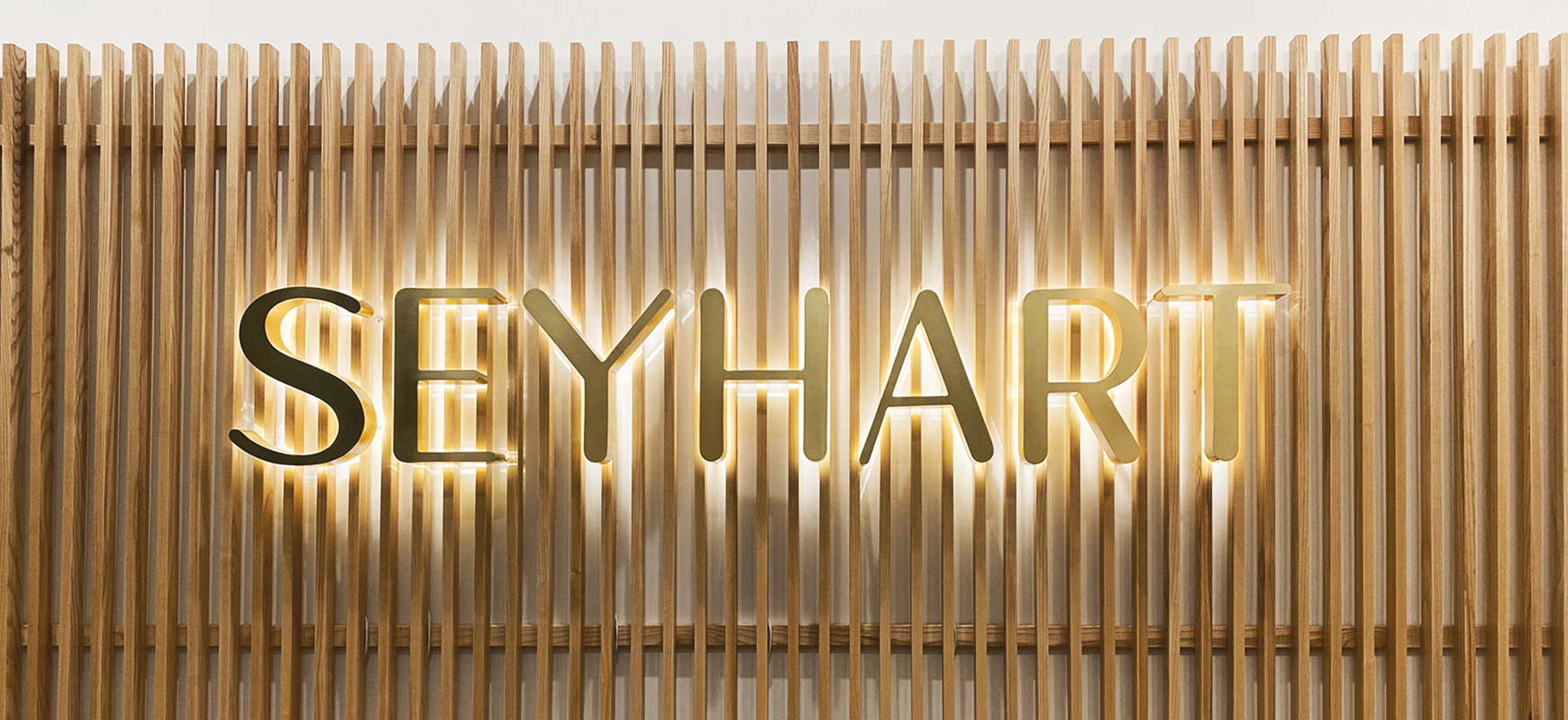 Seyhart channel letters in gold color displaying the company name made of aluminum and acrylic for interior branding