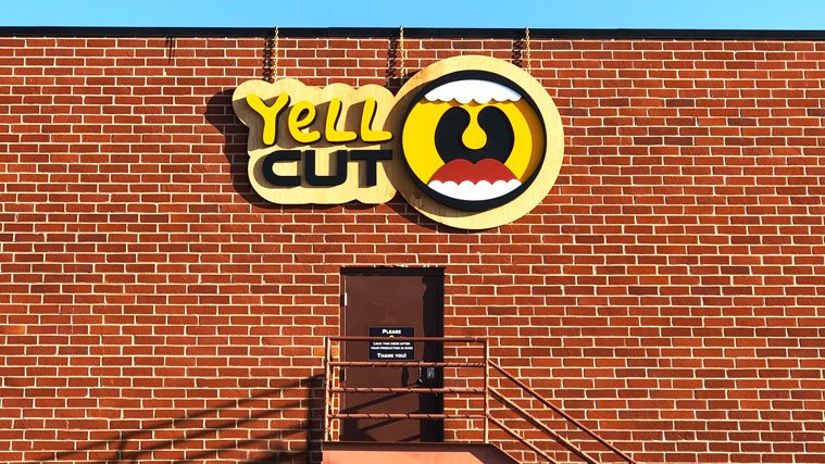 Yell Cut Business Sign hanging with the help of chains