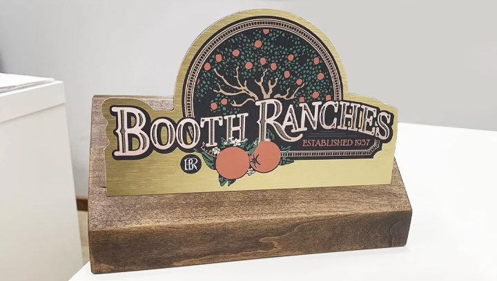 Booth Ranches office desk sign with a custom shape made of wood and brushed aluminum