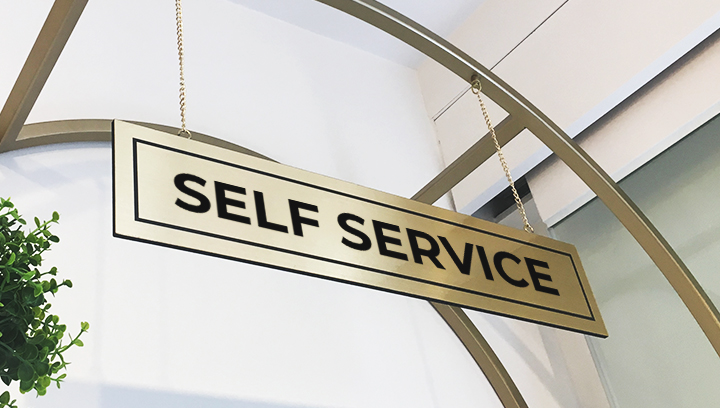 hanging foam core sign in golden color displaying the words Self Service