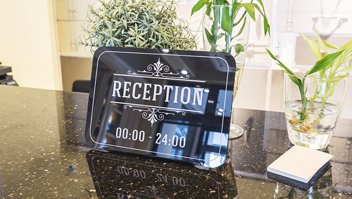 informative lobby sign in black color made of acrylic displayed on the reception desk