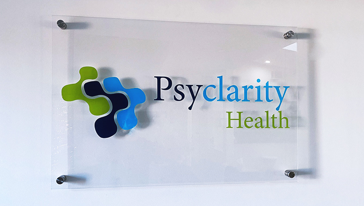 Psyclarity Health plastic lobby sign displaying the company name and logo for office branding