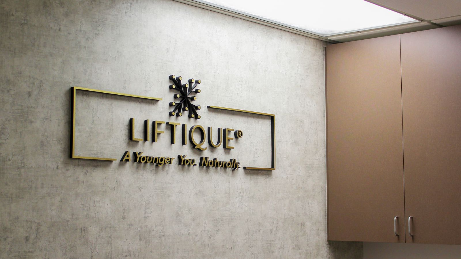 Liftique Clinic office lobby logo sign and slogan made of aluminum and acrylic for interior branding