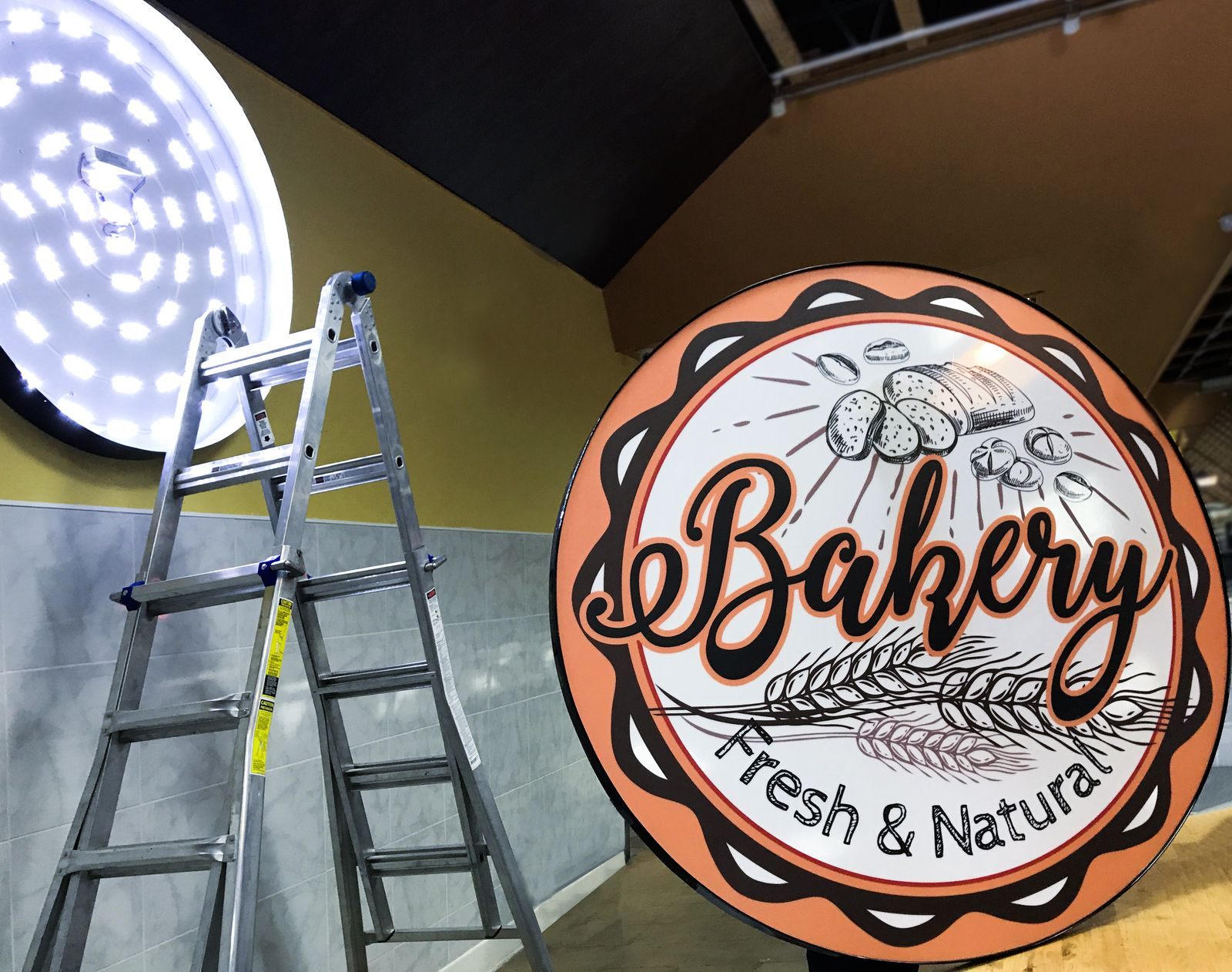 Bakery light box sign in a round shape made of aluminum and covered with acrylic and backlit vinyl during the installation