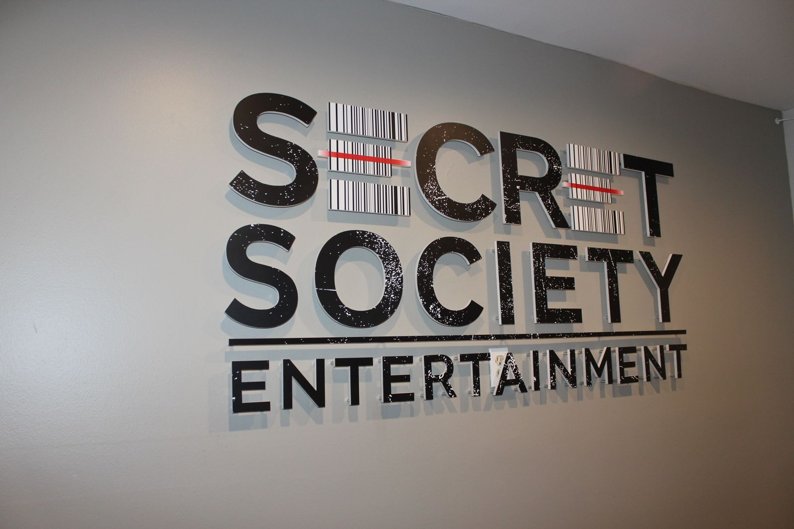 Secret Society Entertainment interior business sign with the company name made of acrylic for company branding indoors
