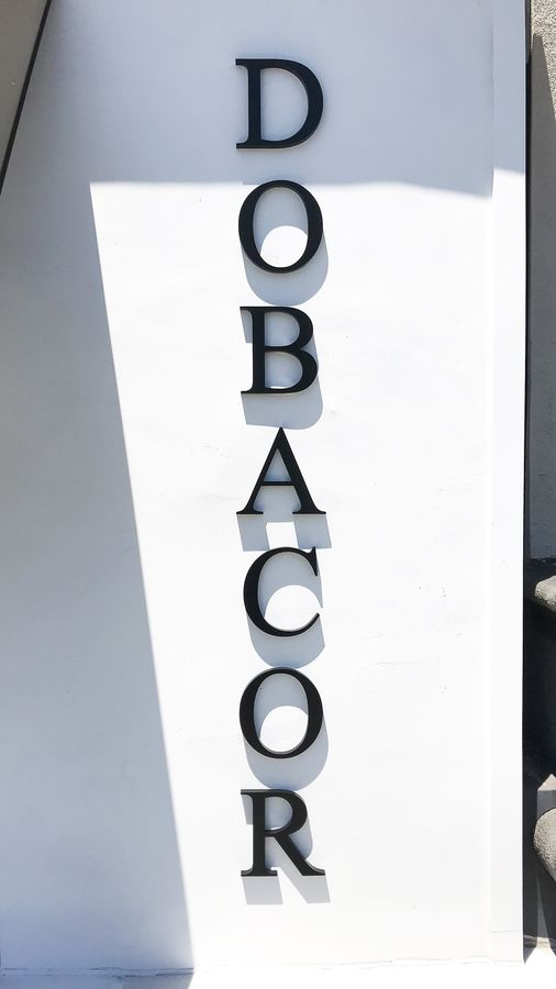 Dobacor 3d acrylic letters in black color with the company name fixed to the building for exterior branding