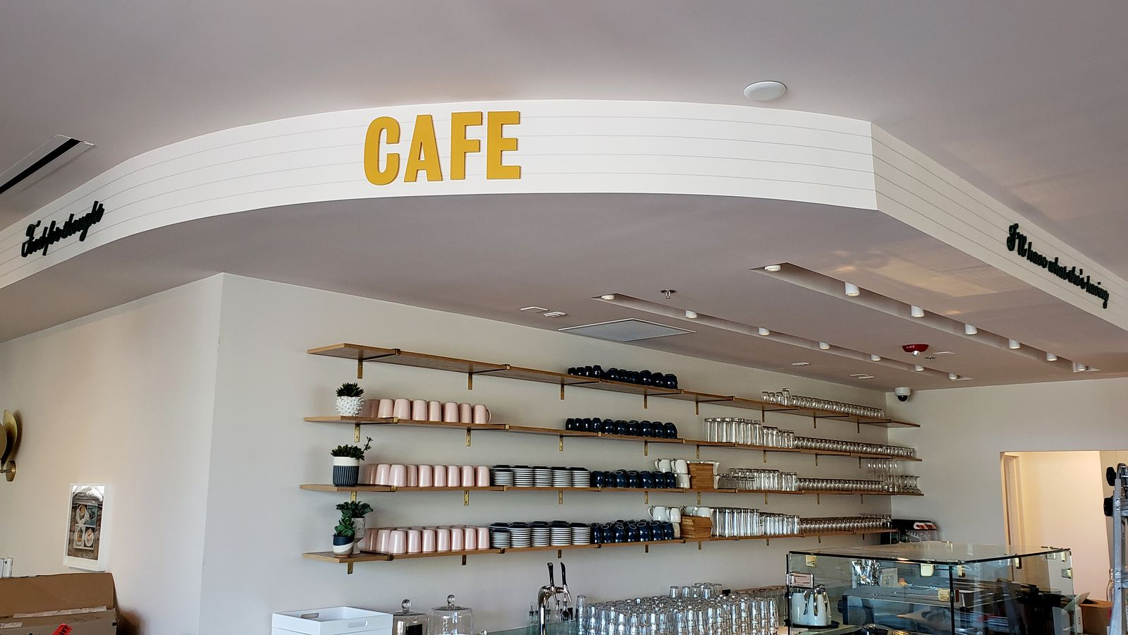 painted 3d acrylic letters in yellow color with the word Cafe fixed to the wall for restaurant interior branding