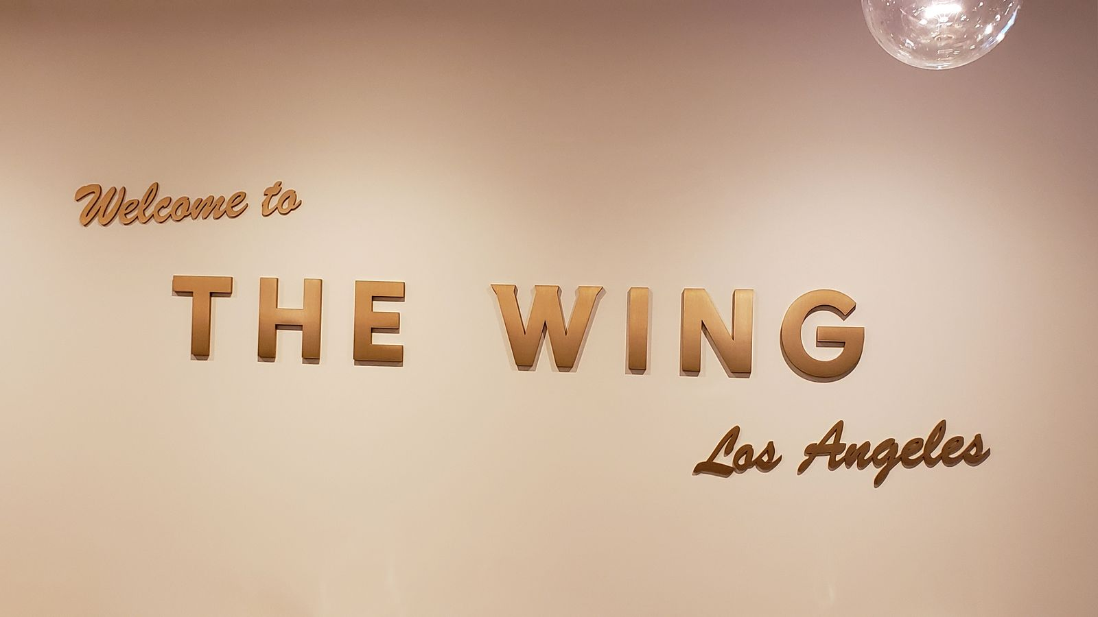 The Wing 3d acrylic letters painted in gold color with Welcome to The Wing Los Angeles message for office lobby branding
