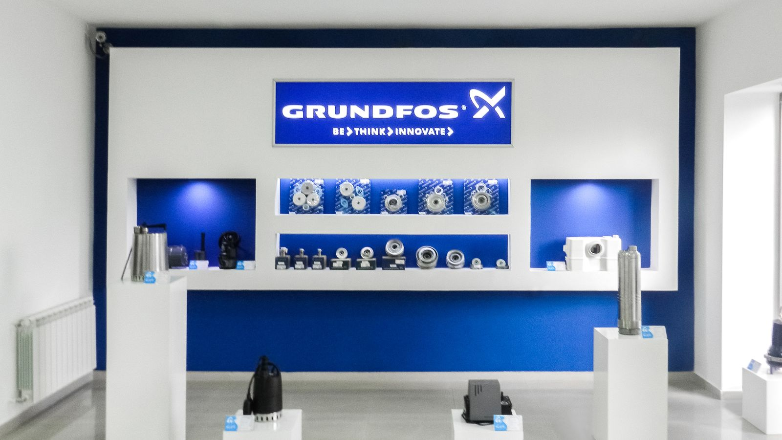 Grundfos illuminated interior signage with the company name, logo and slogan made of acrylic and aluminum for store branding