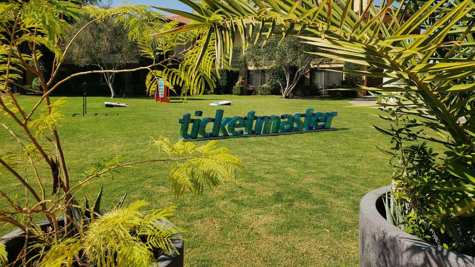 Ticketmaster 3d acrylic letters stand sign in green color on a grass displaying the company name for outdoor event branding