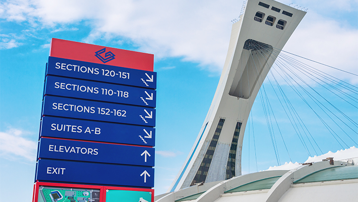 huge stadium wayfinding signage in blue and red displayed outdoors