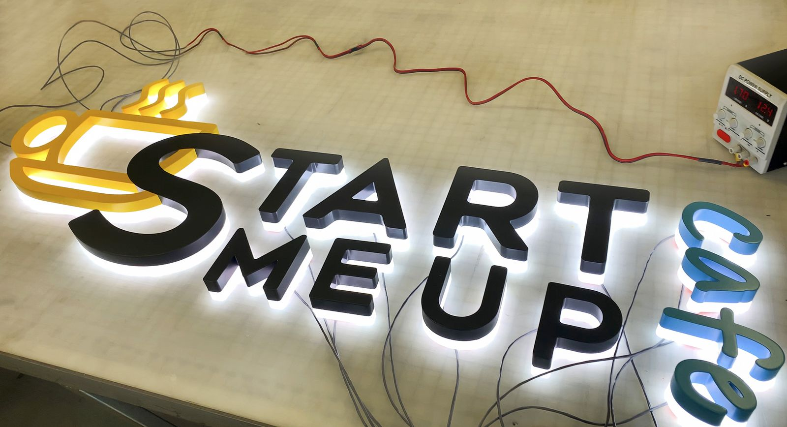 Start Me Up Cafe backlit 3d sign displaying the company name and logo made of acrylic