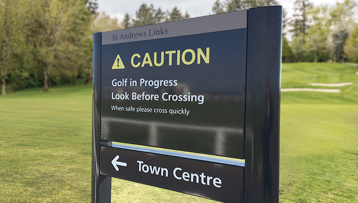 black golf event sign displaying warning and directional messages
