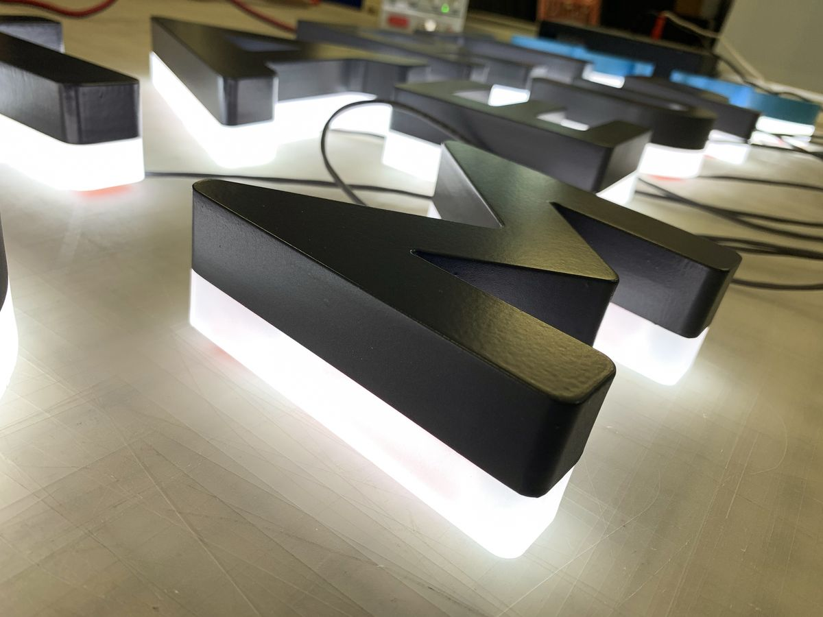 Backlit 3d acrylic letters painted in black color displayed on the table before installation