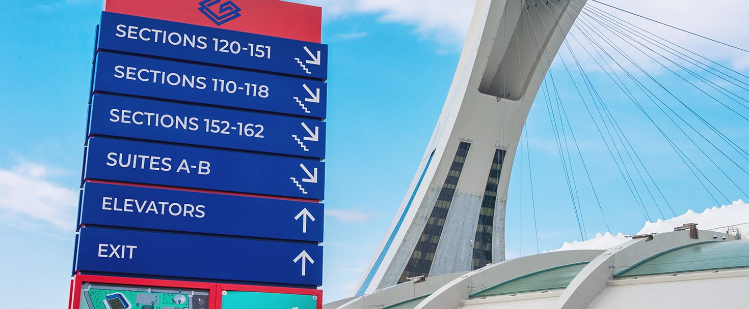 large stadium wayfinding signage in blue and red displayed outdoors