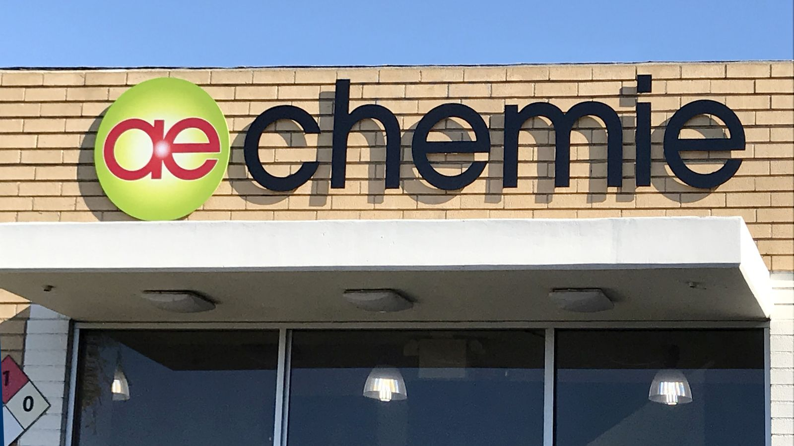Chemie 3d metal logo sign in green and red colors and letters in black made of aluminum for storefront branding