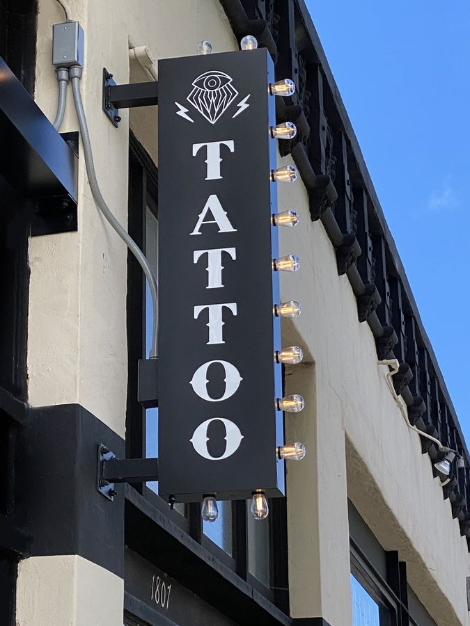 wall-blade outdoor light box with clear light bulbs attached to it made of aluminum and acrylic for tattoo store branding