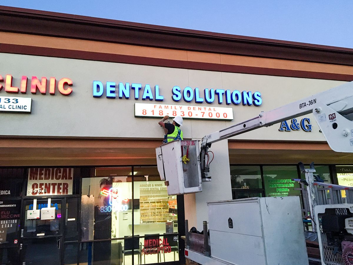 Dental Solutions led light boxes displaying business contact number made of acrylic and aluminum during the installation