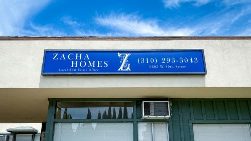 Zacha Homes acrylic light box with the company name and contact details for real estate office storefront branding