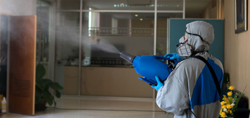 Man in protective clothing disinfecting workspace after business reopening