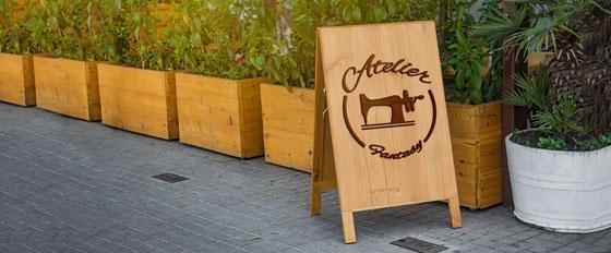 Atelier Fantasy sandwich board design with cool wood cut patterns