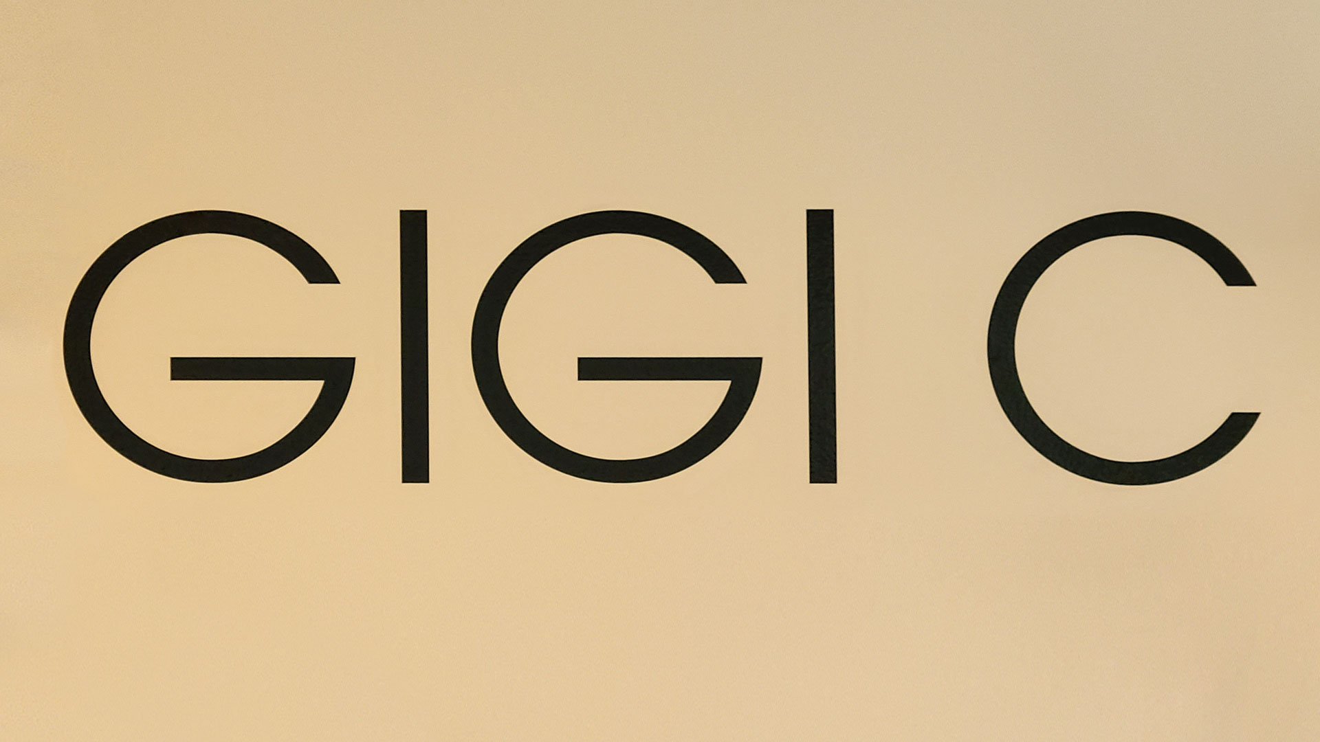 Gigi C custom interior wall lettering signage with the name of the company made of opaque vinyl for clothing store branding