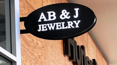 AB & J Jewelry light box sign in an oval shape displaying the company name made of aluminum and acrylic for brand visibility