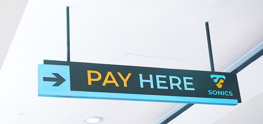 'Pay Here' sign with the brand's name as a corporate branding tip