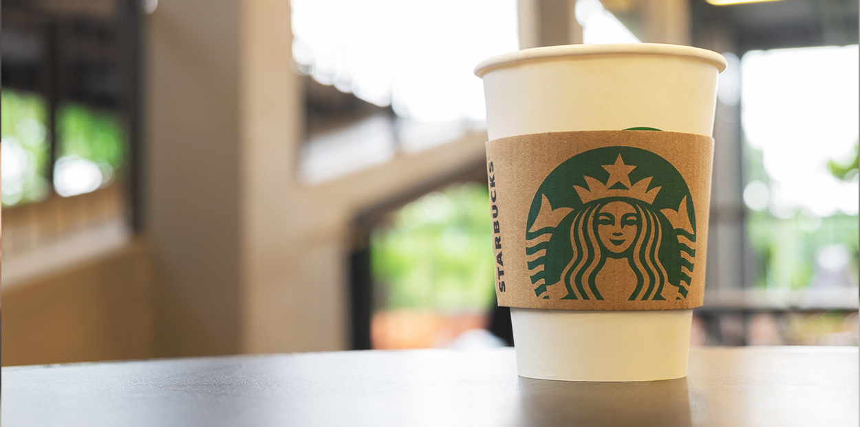 Starbucks eco friendly cup showing it's green business practice example