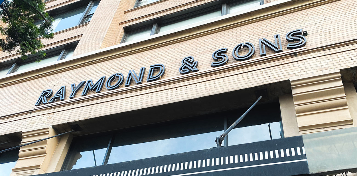 Raymond & Sons storefront branding with metal materials