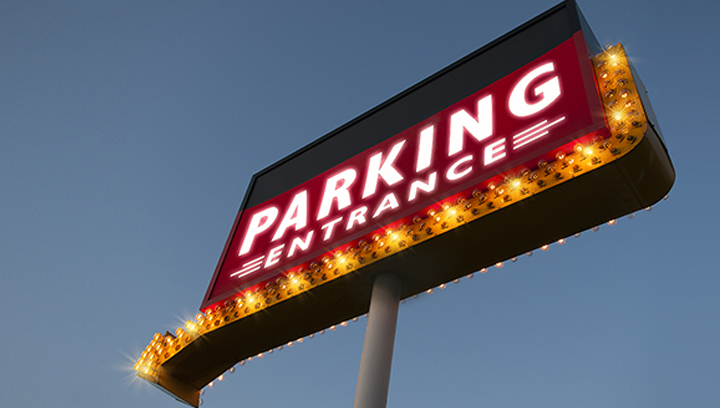 illuminated high rise sign with a directional arrow displaying the words Parking Entrance