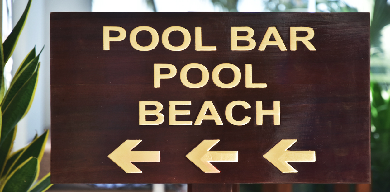 Beach directional sign made of wood pointing at the beach, pool, and the bar