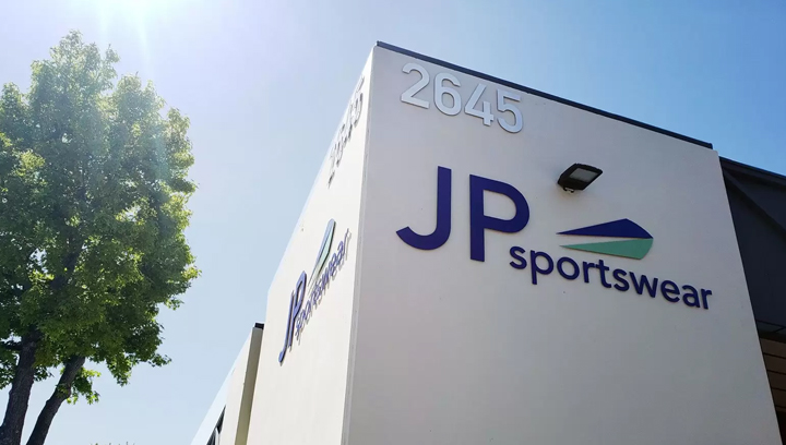 JP Sportswear building top sign displaying the brand name and logo made of aluminum