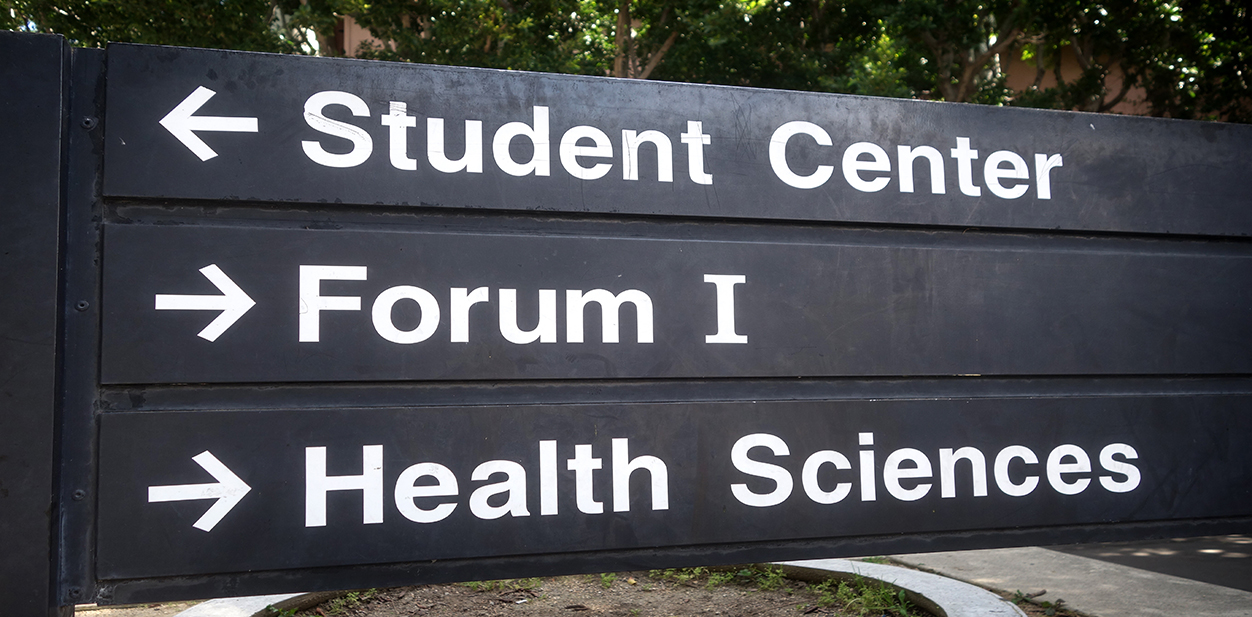 College wayfinding sign in black pointing at different departments