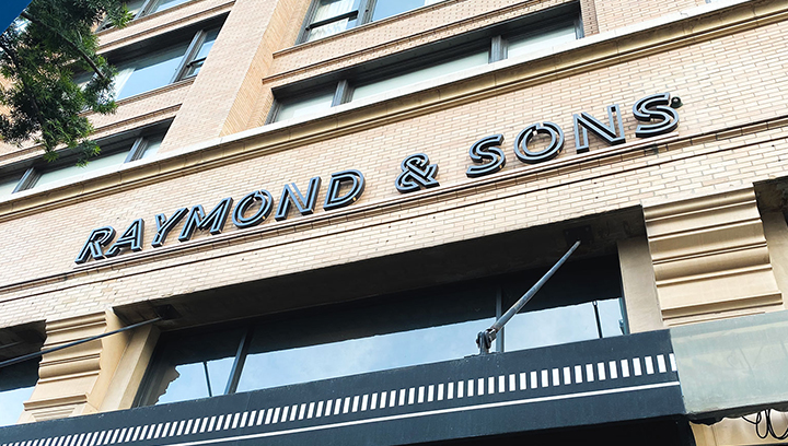 Raymond & Sons office building sign displaying the brand name made of aluminum