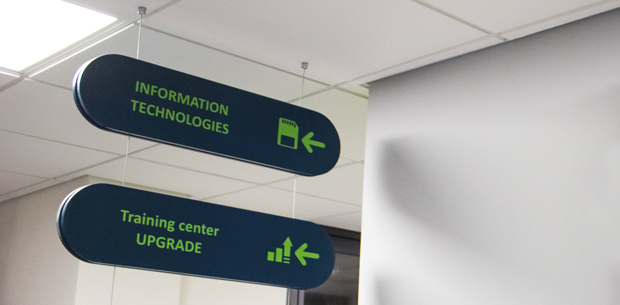 Custom hanging directional sign in dark blue made of PVC and opaque vinyl