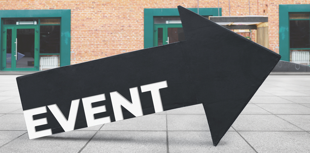 Large event directional signage in an arrow shape and in black color