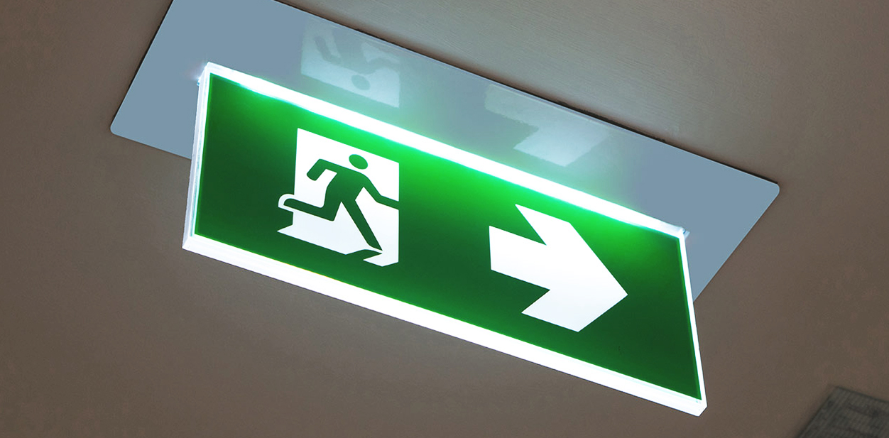 Illuminated directional exit sign in green made of acrylic