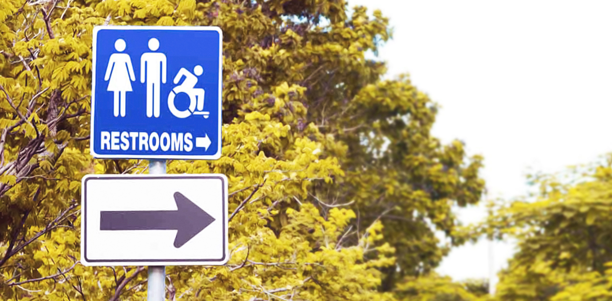 Outdoor informational wayfinding signs made of aluminum pointing at the restrooms