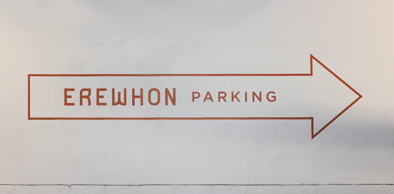 Wall wayfinding sign pointing at the parking made of opaque vinyl