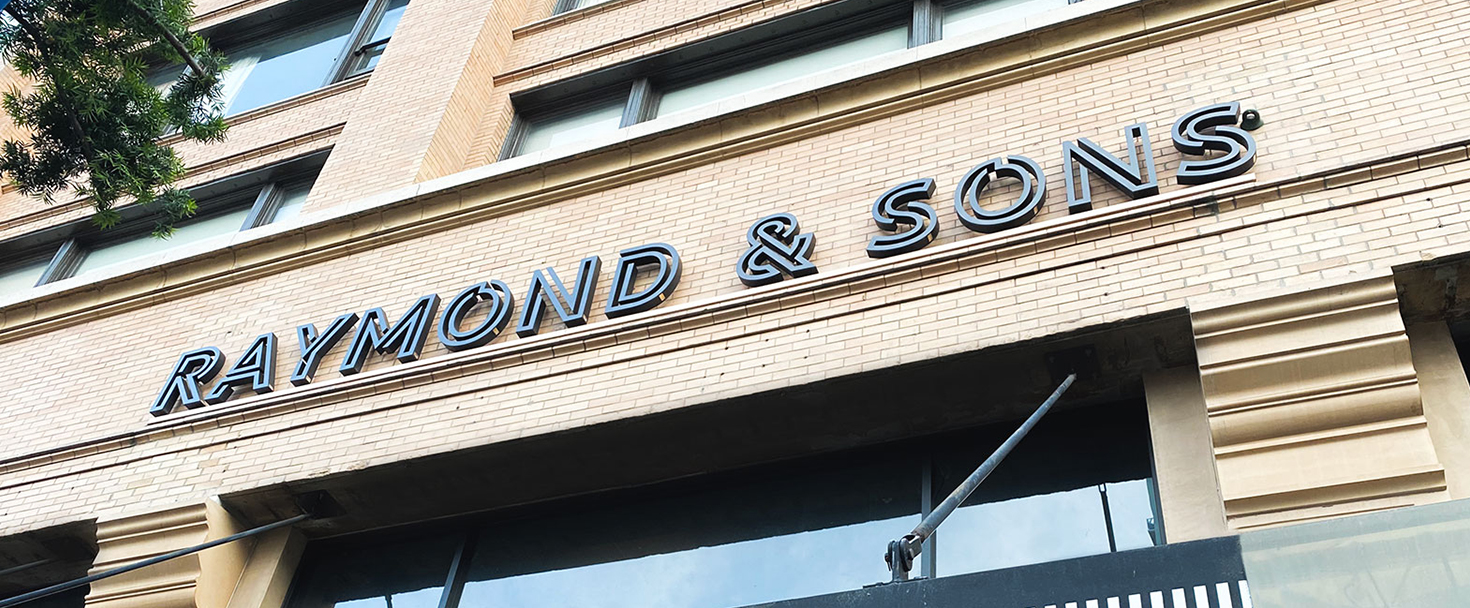 Raymond & Sons building sign displaying the brand name made of aluminum for store branding
