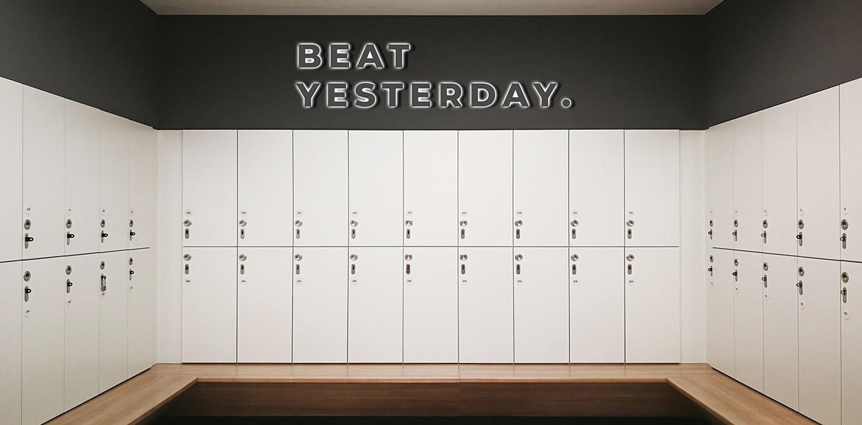 Illuminated gym locker room design idea displaying a motivational phrase