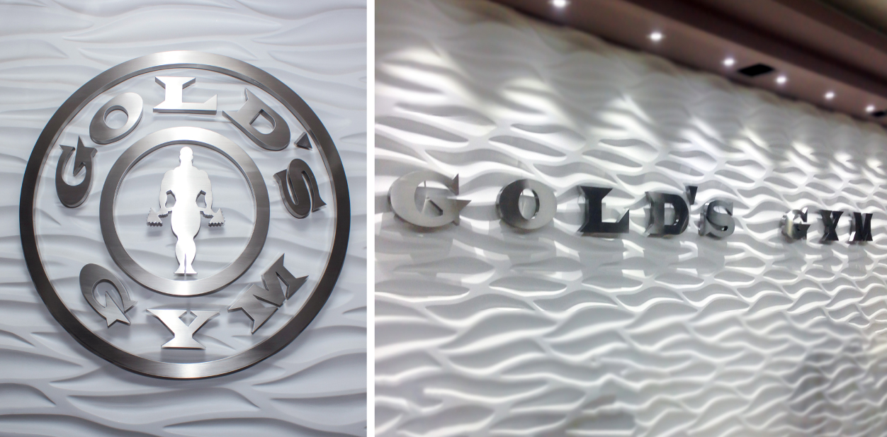 Gold's Gym lobby branding signs with a brushed finish