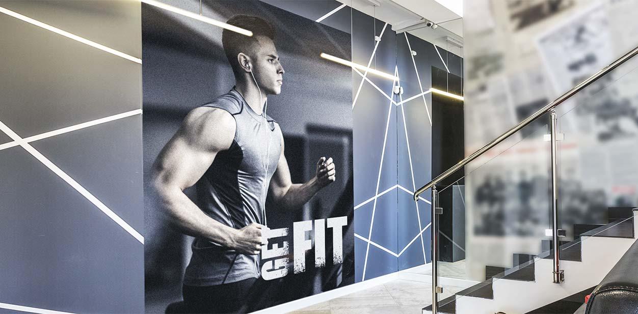 Gym lobby wall design idea with a photograph display and illumination