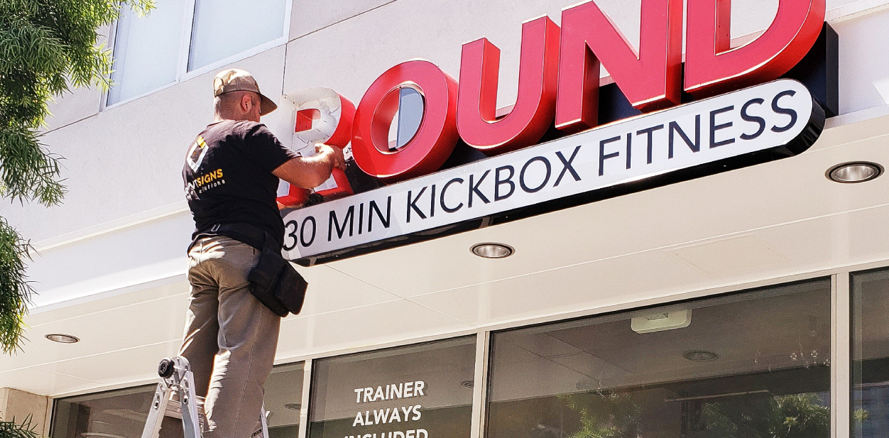 The installation process of 9 Round's gym sign