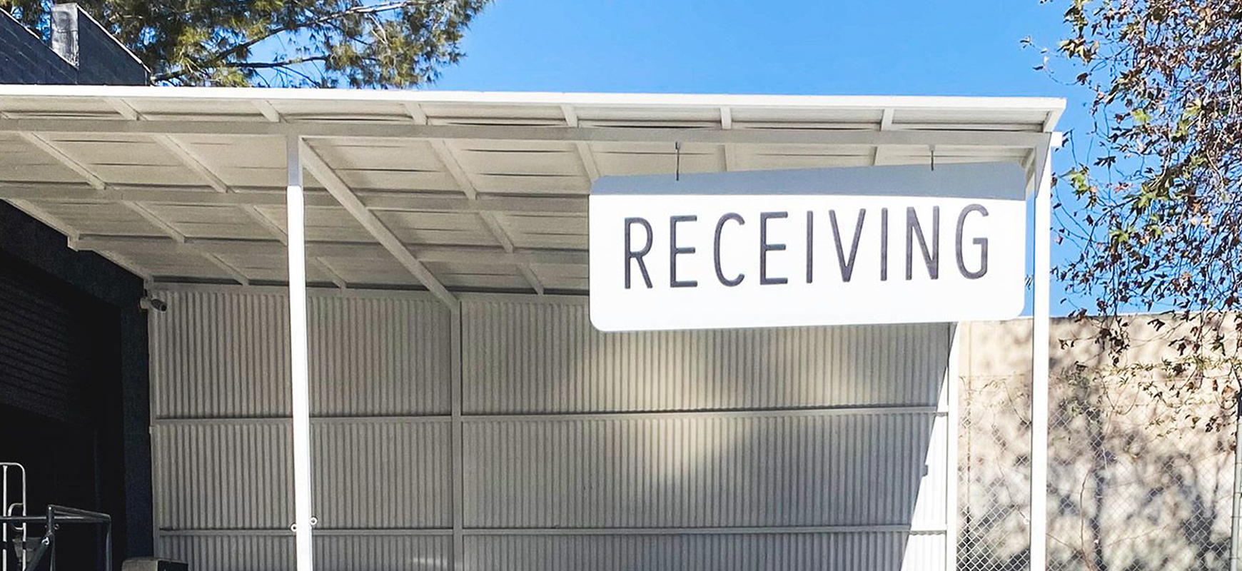 a white-colored hanging outdoor sign displaying the word Receiving